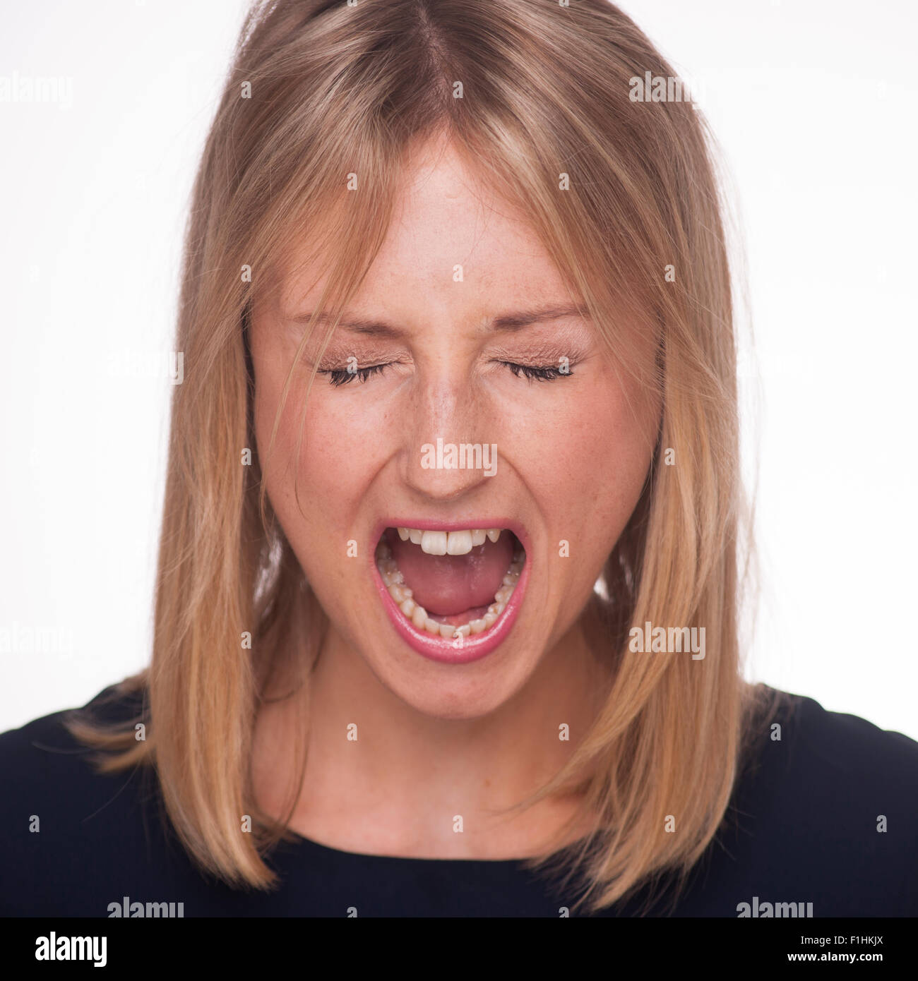 Blonde woman yelling with her eyes closed. - Stock Image