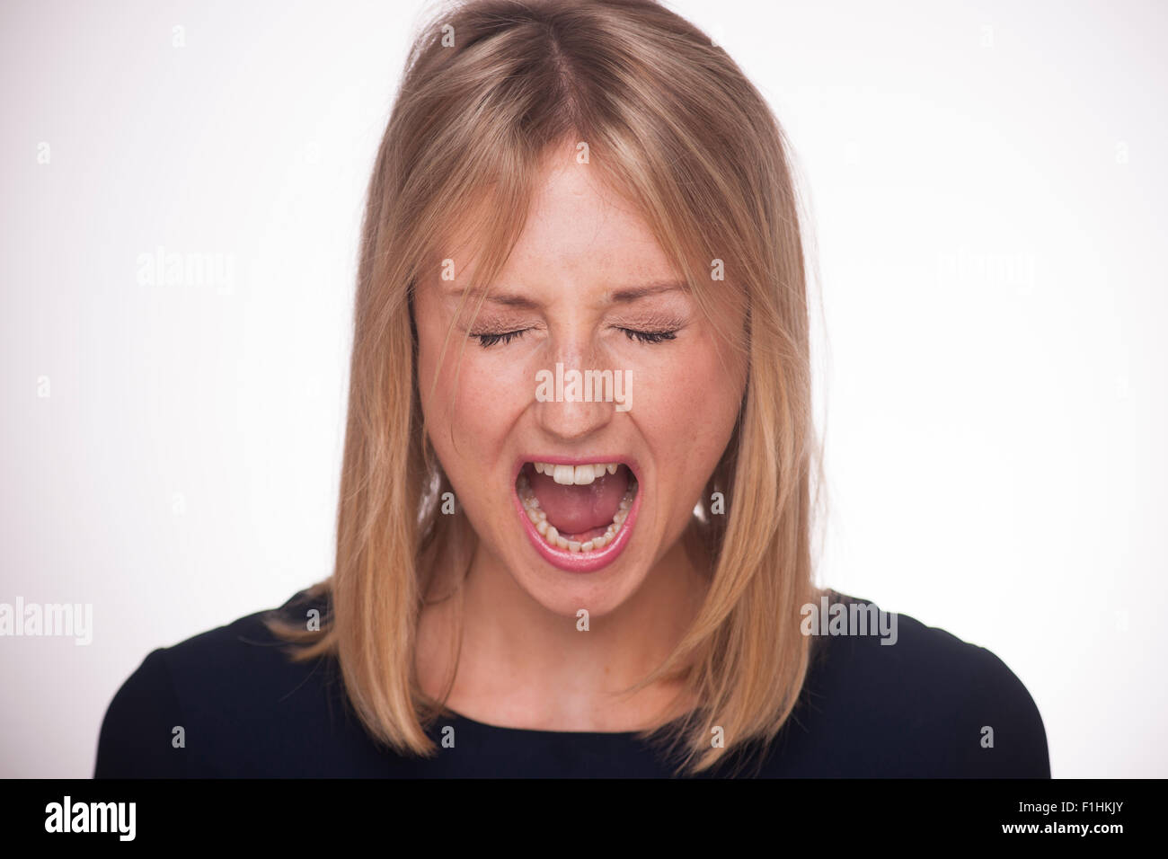 Blonde woman yelling screaming with her eyes closed. - Stock Image