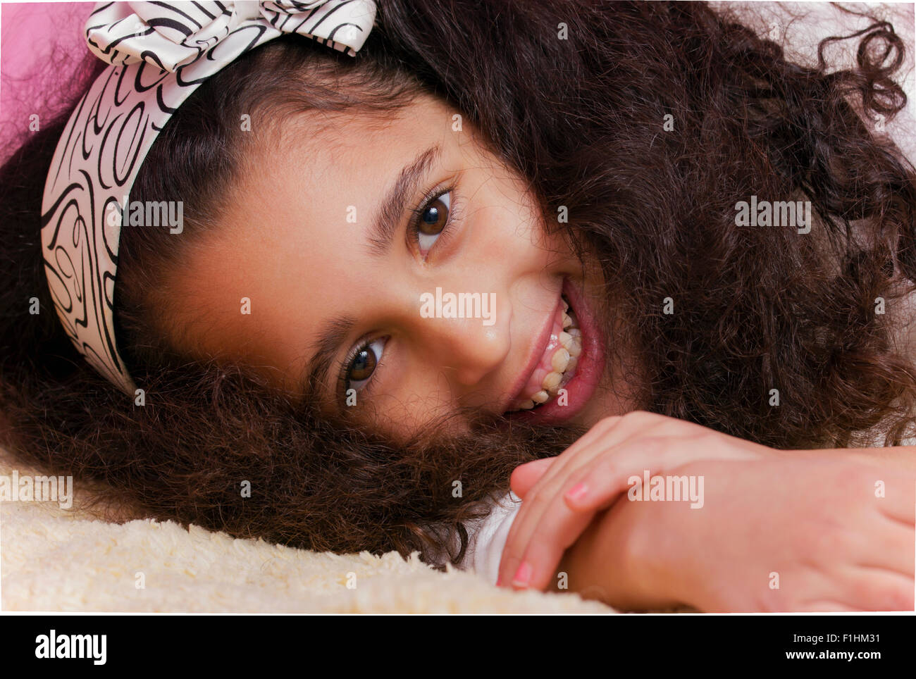 Smiling child brunette swarthy girl lying in the bed - Stock Image