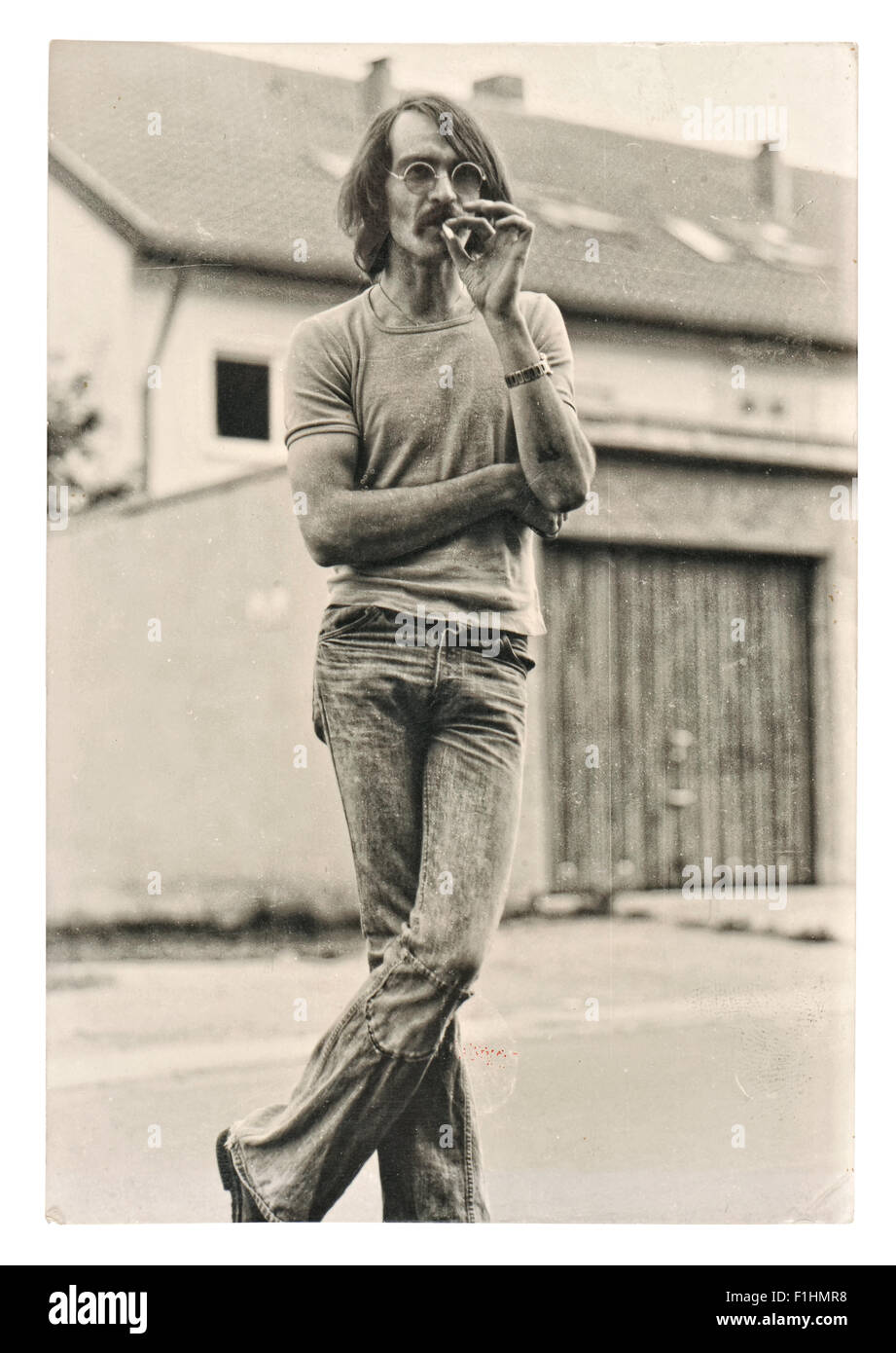Vintage photo from young fashion smoking man wearing typical 1970s clothing. - Stock Image