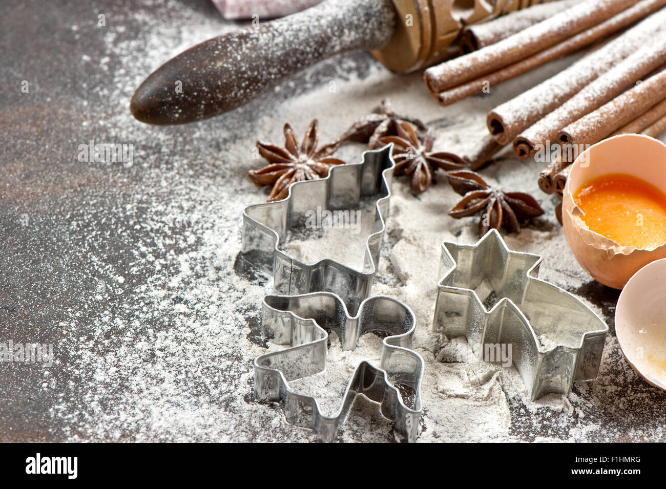 Baking ingredients and tolls for dough preparation. Flour, eggs, rolling pin and cookie cutters. Christmas food - Stock Image