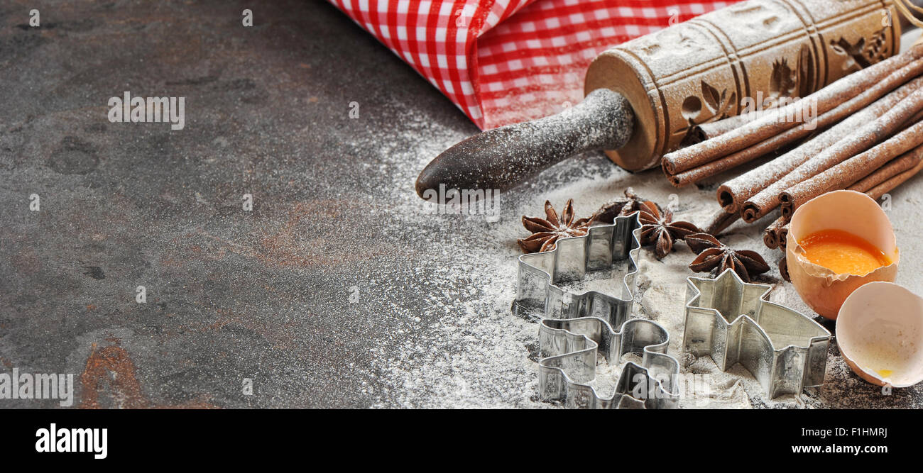 Christmas food. Baking ingredients and tolls for dough preparation. Flour, eggs, rolling pin and cookie cutters - Stock Image