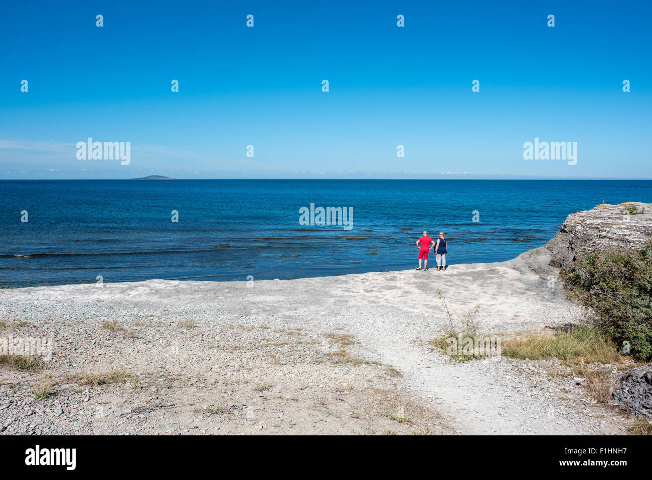 Tourists at Byrum on northern Oland enjoy the view of the Baltic Sea and island Blue Virgin. - Stock Image