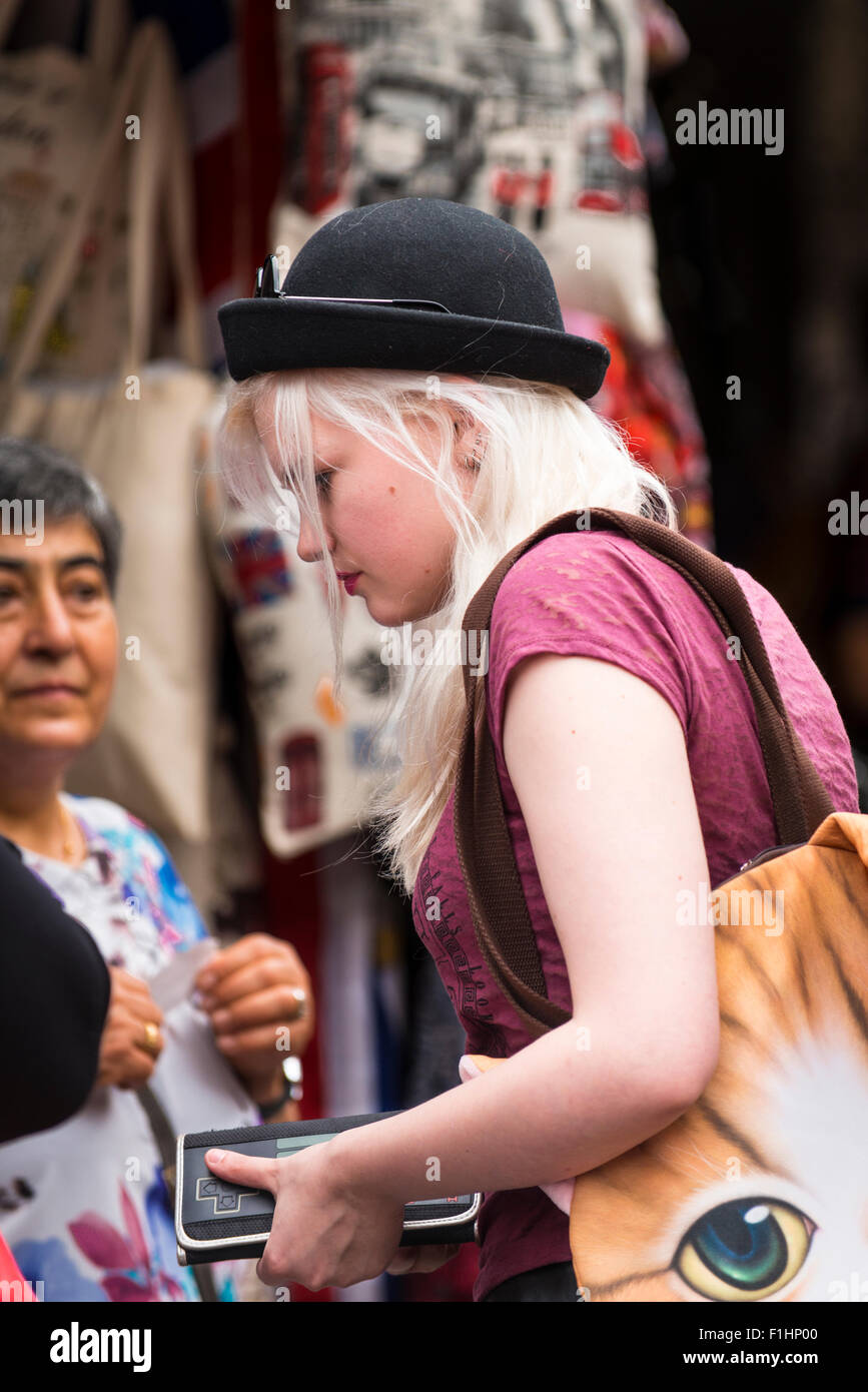 London , Camden Town , Stable Market pretty young girl white blond hair , bowler hat , tabby cat shoulder bag checks Stock Photo