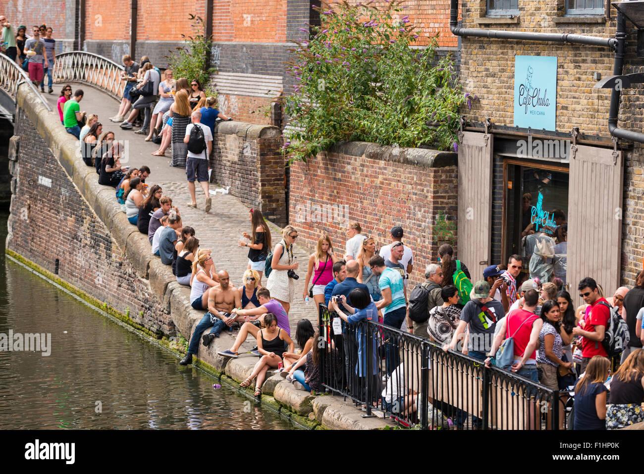 London , Camden Town , Regents Canal , tourists people crowds enjoy summer sun by water , bridge & market entrance Stock Photo