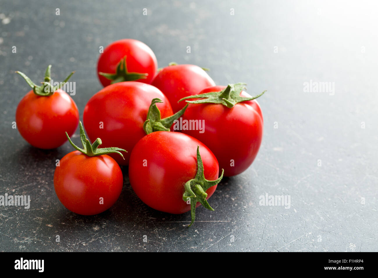 red tomatoes on kitchen table - Stock Image