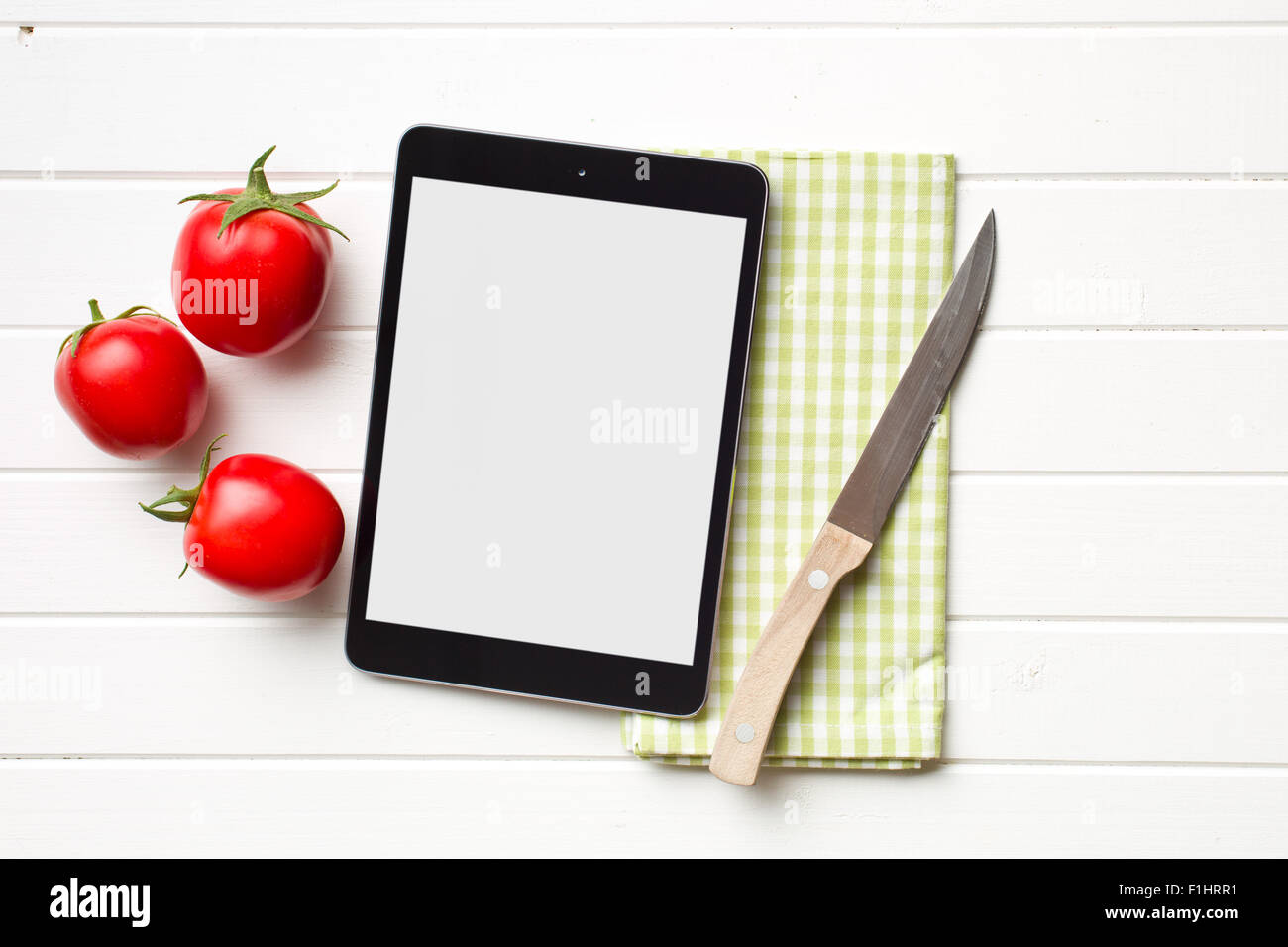 computer tablet and tomatoes on kitchen table - Stock Image