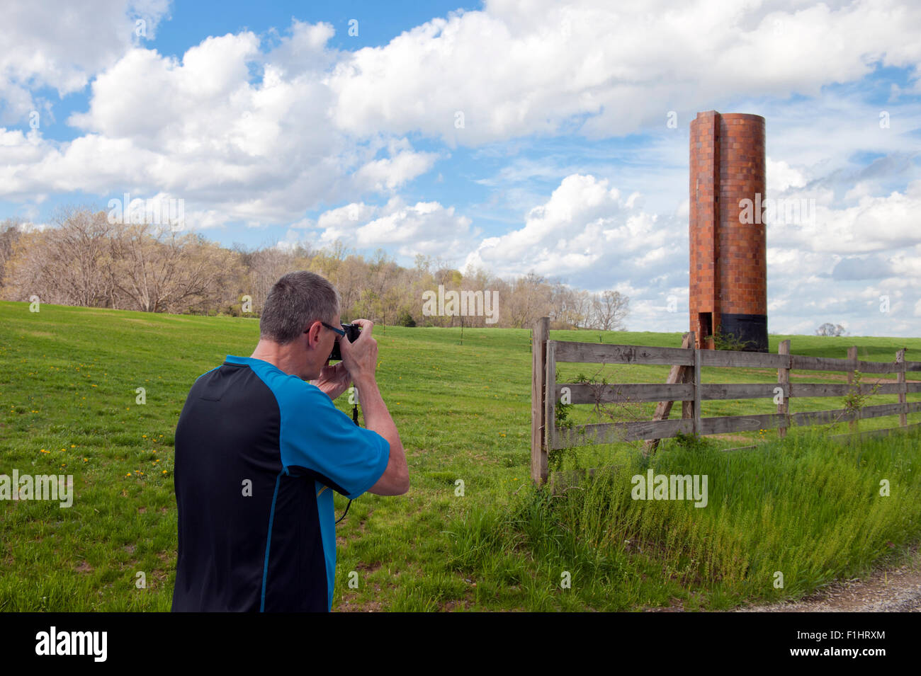 Photographer taking a picture of an old unused tile silo in Shenandoah Valley, Virginia USA. - Stock Image