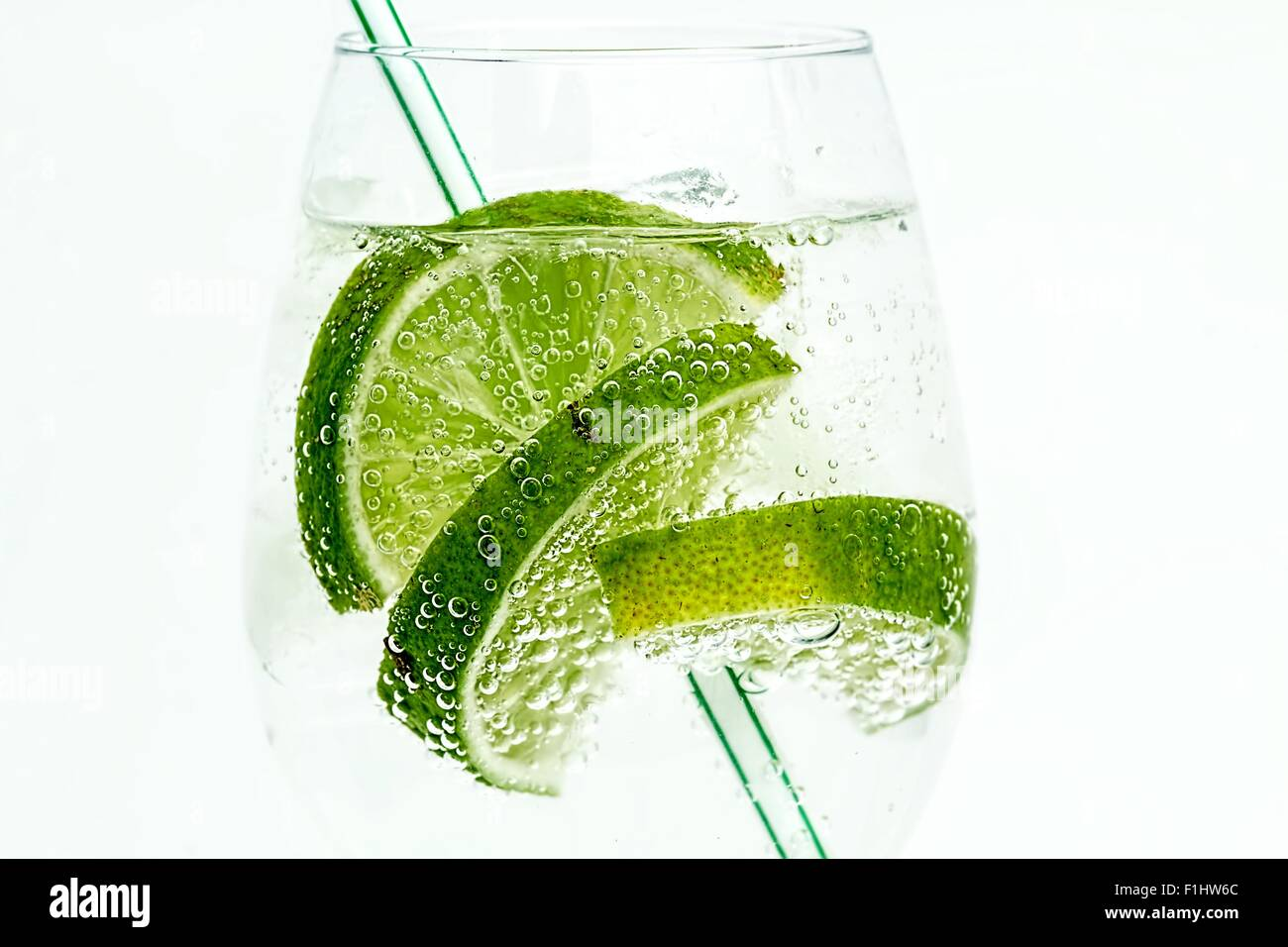 Slices of lime in a glass of fizzy drink with a straw on a white background - Stock Image