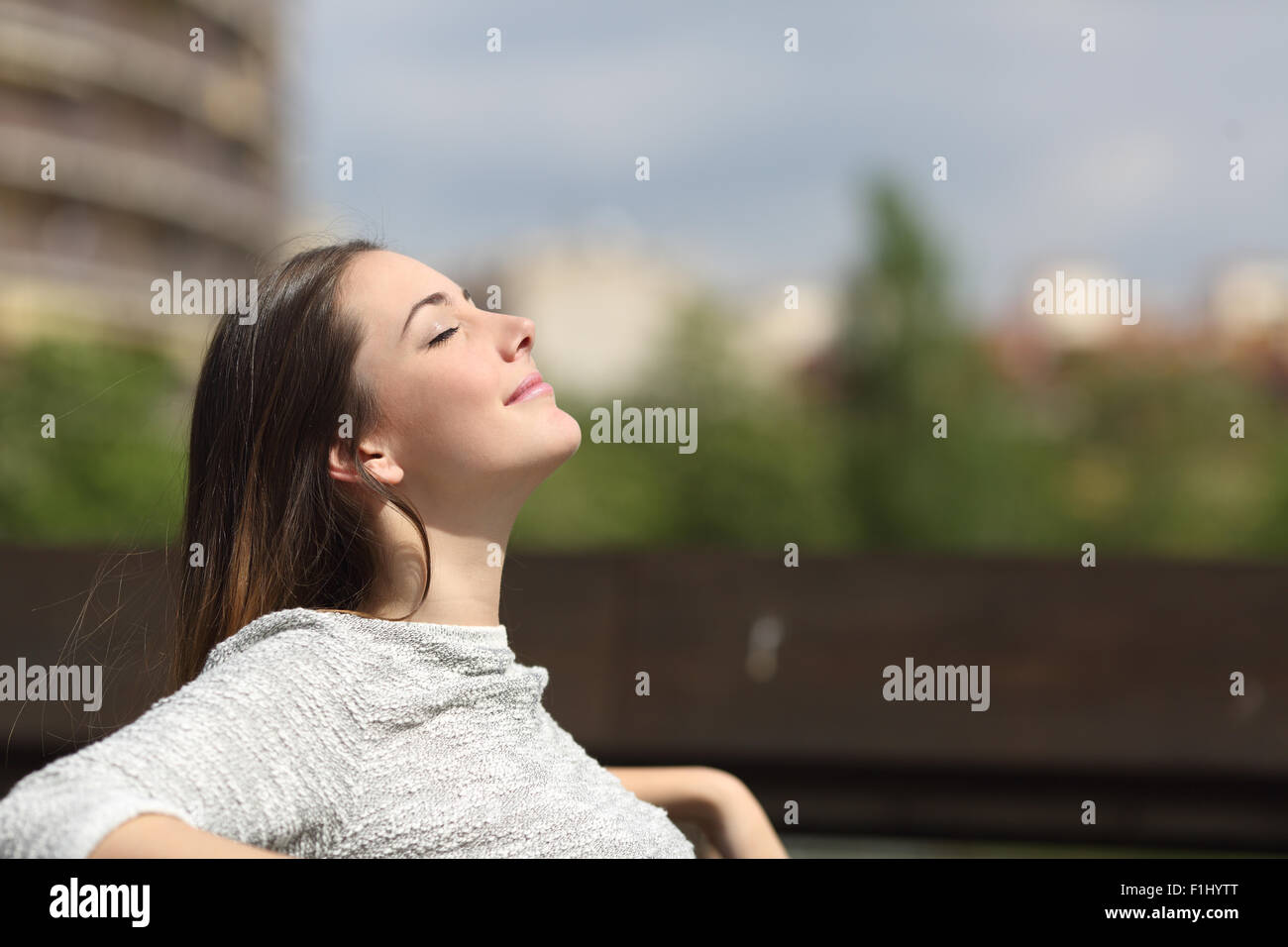 Urban woman sitting on a bench of a park and breathing deep fresh air - Stock Image