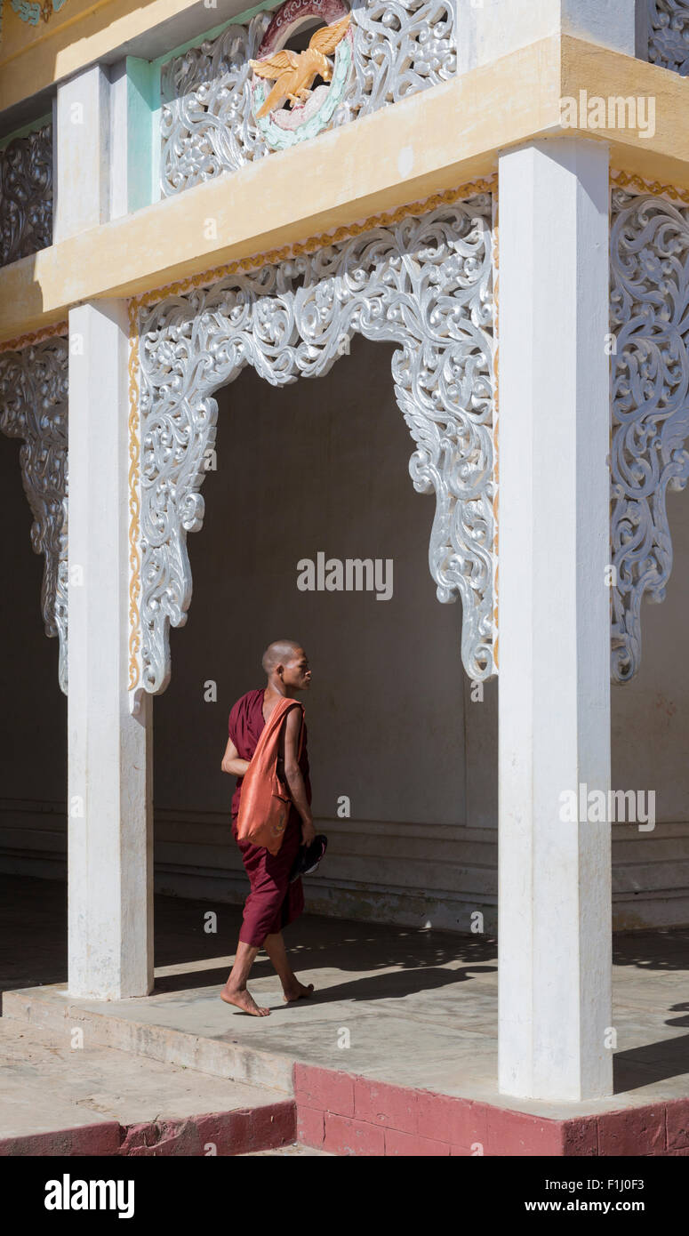 Buddhist monk entering colonnade decorated with ornate screen at Schwezigon paya, Nyaung U, Myanmar near temples - Stock Image