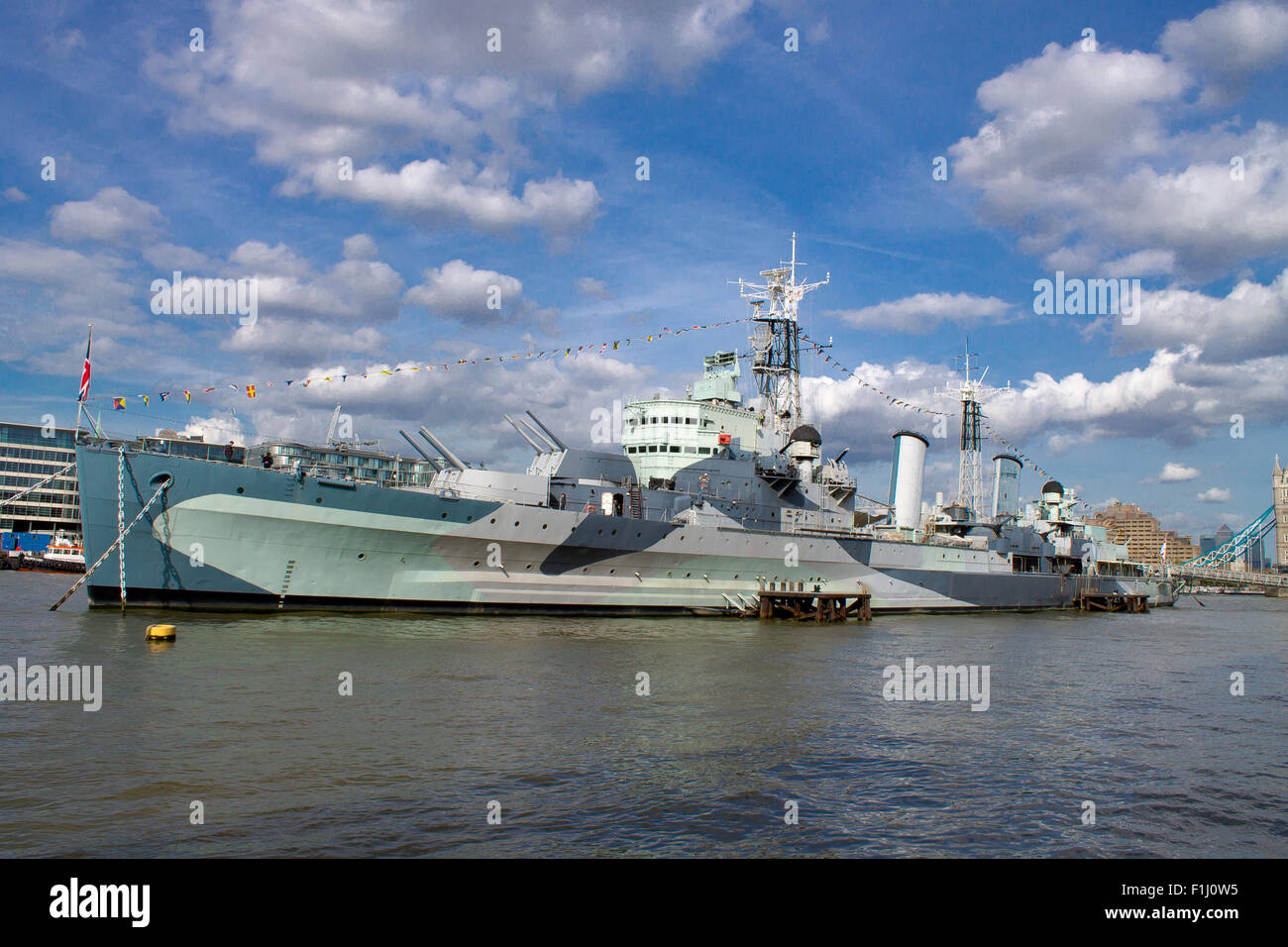 HMS Belfast, famous warship on River Thames. London City on a background. Tourists walking on the deck of the ship. - Stock Image