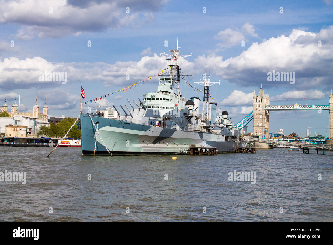 HMS Belfast, famous warship on River Thames. Tower Bridge on the background. - Stock Image