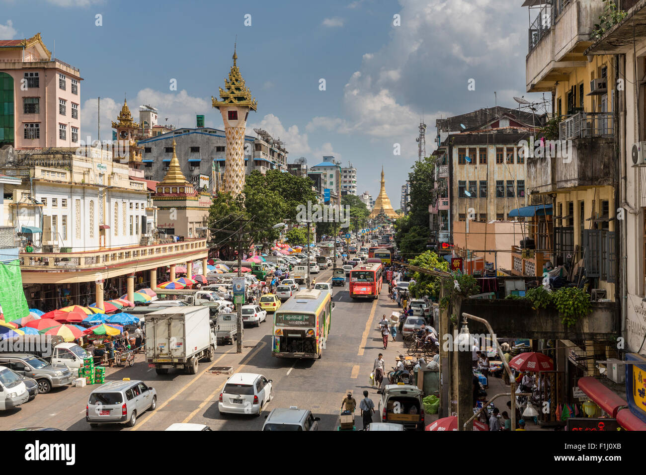 Bustling Mahabandoola Rd, Yangon, Myanmar. The city market is on the left and Sula Pagoda at the end of the street. - Stock Image