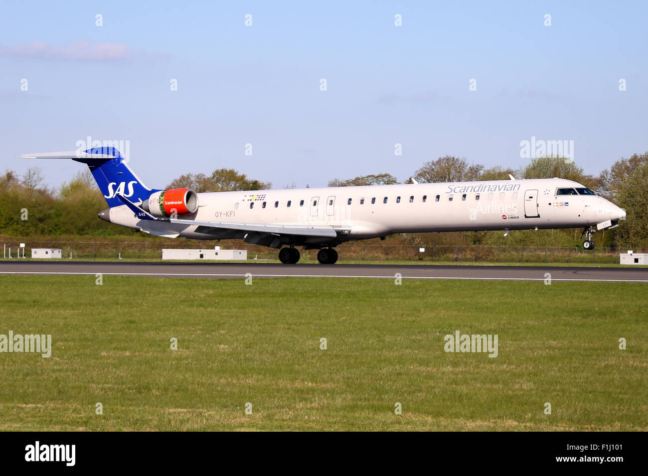 Scandinavian Airlines (SAS) Bombardier CRJ-900 touches down on runway 05L at Manchester airport. - Stock Image