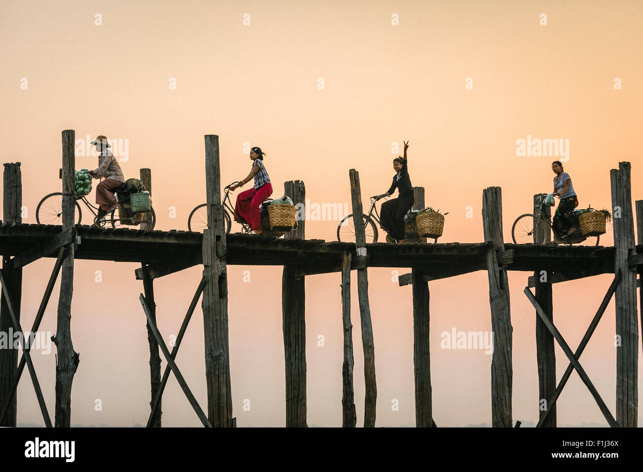 Burmese woman flashes peace sign on a bike riding over U Bein Bridge at sunset.  U Bein Bridge Burma, Myanmar - Stock Image