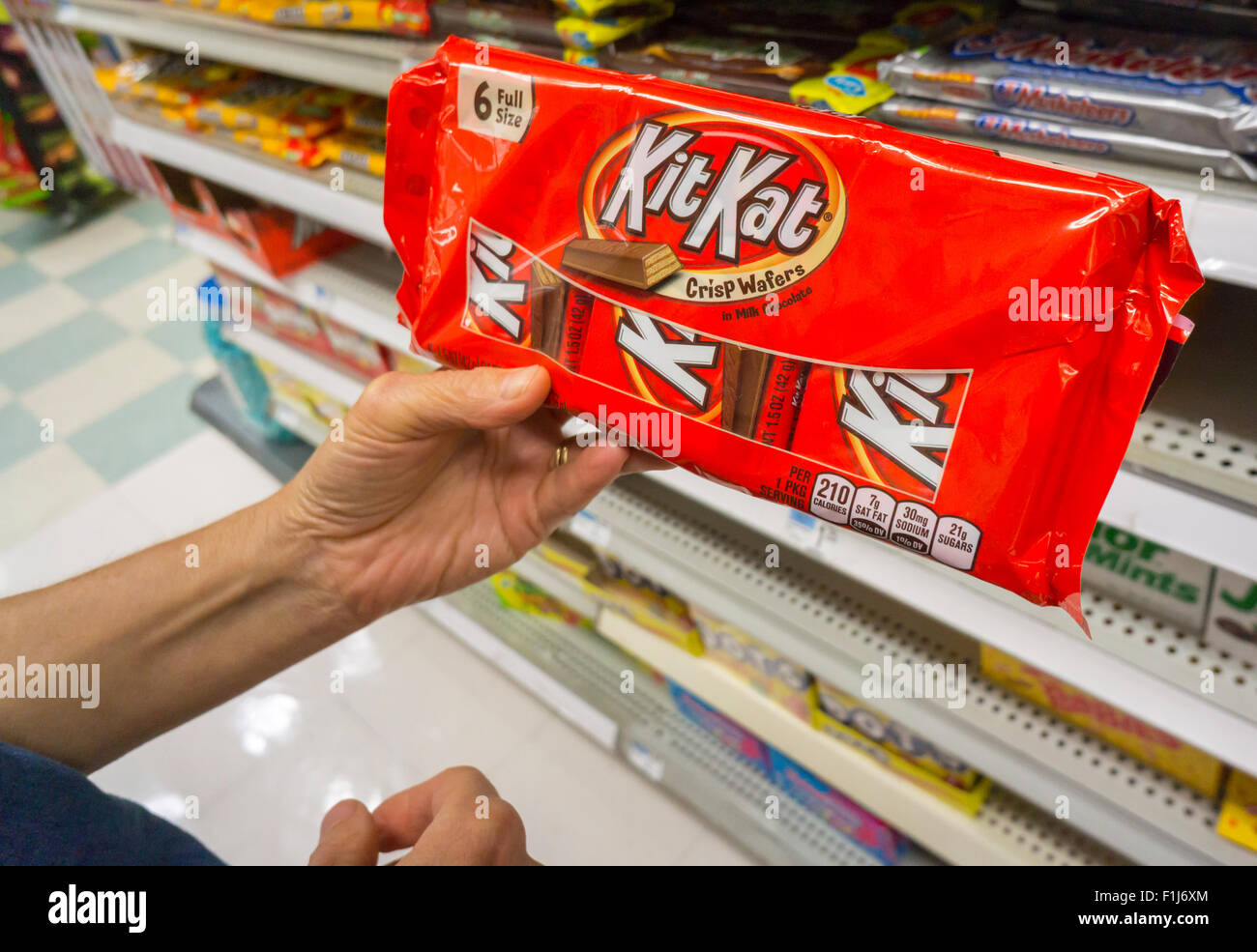 A shopper chooses a bag of Nestlé's KitKat brand chocolate candy in a store in New York on Monday, August - Stock Image