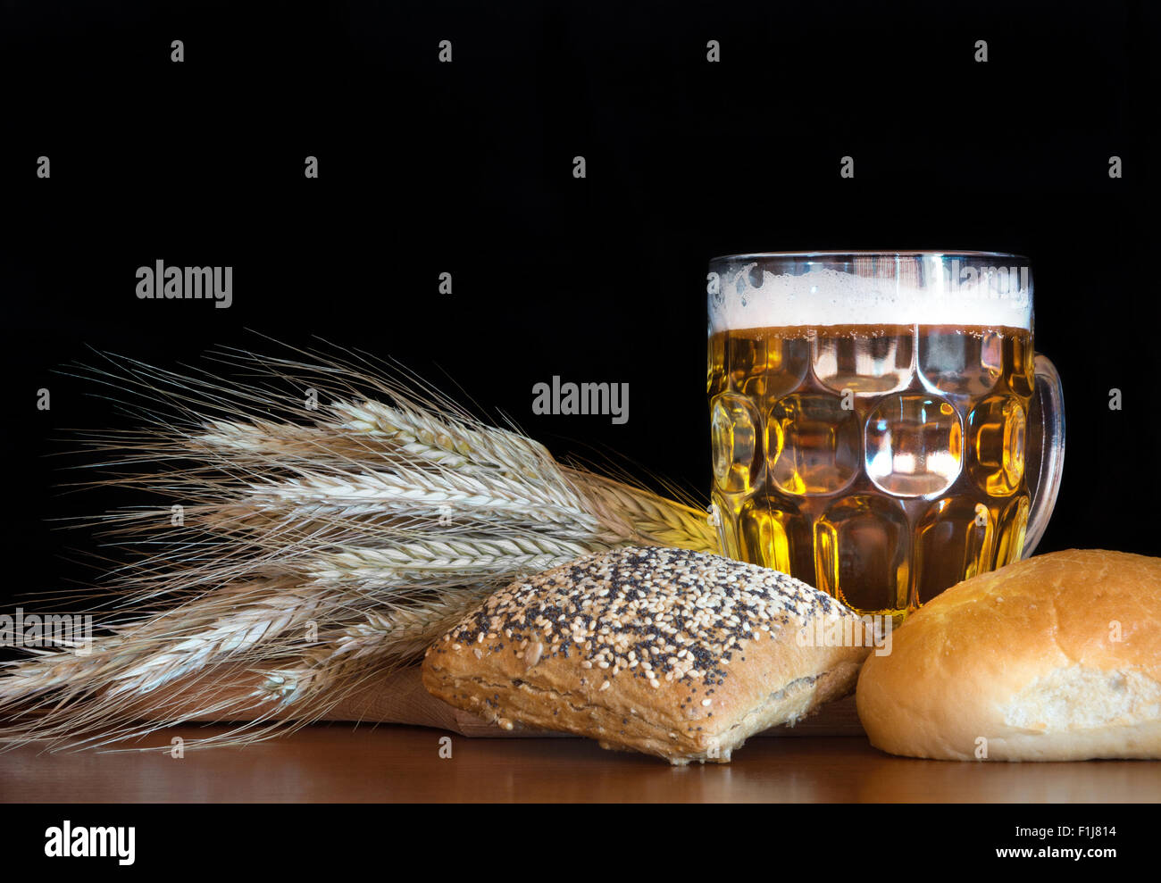 Pint of beer with wheat on black background. - Stock Image
