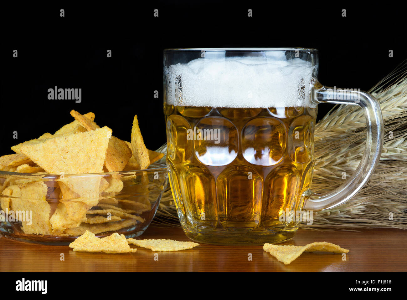 Pint of beer and chips with wheat on black background. - Stock Image