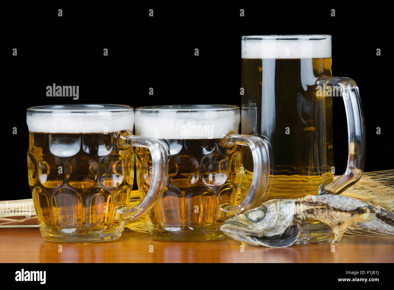 Pint of beer and mackerel with wheat on black background. - Stock Image