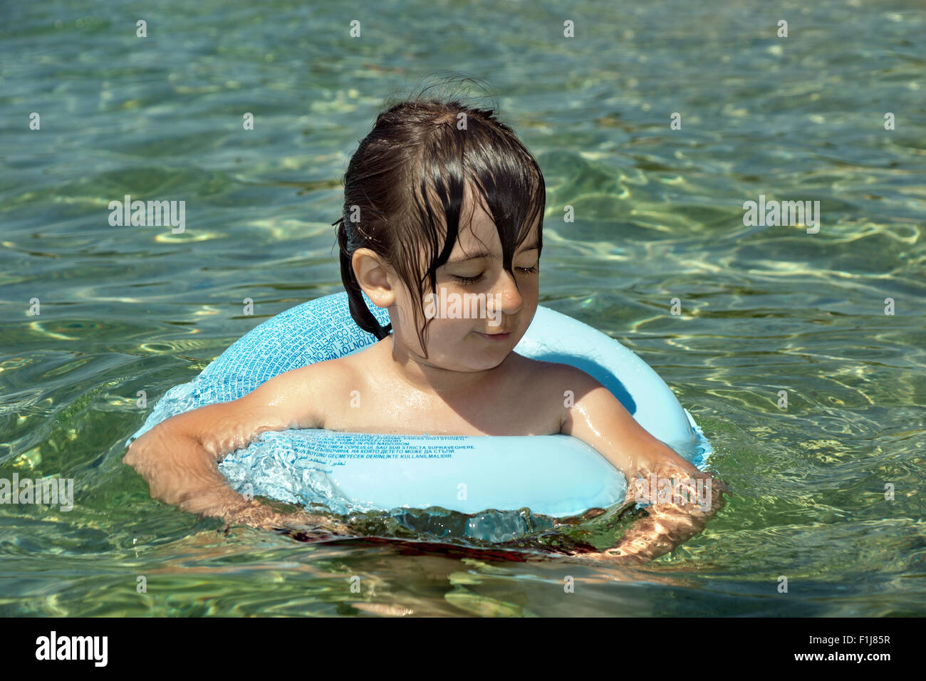 Child with floating ring having fun in the sea - Stock Image