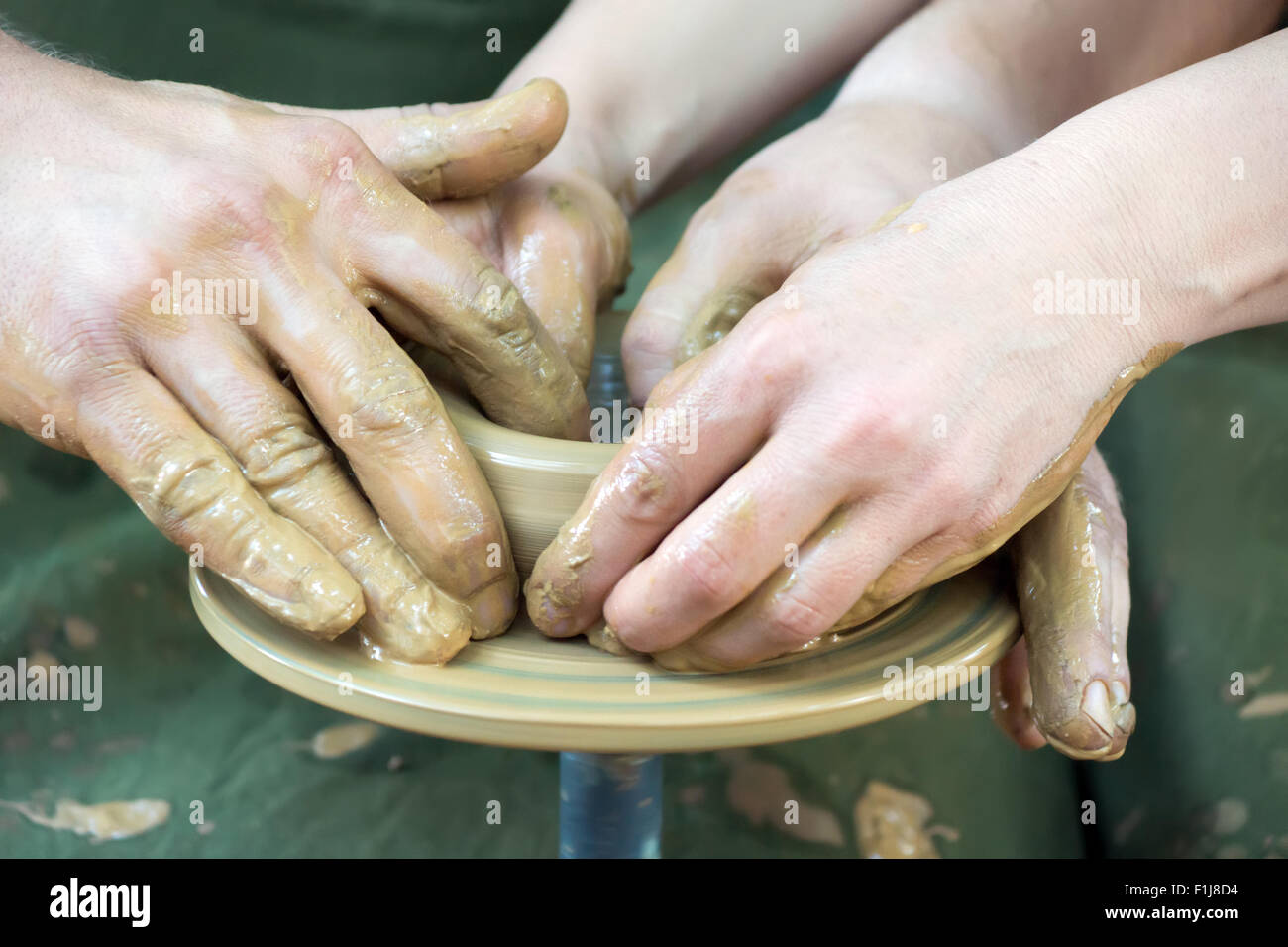 A potters hands guiding a novice hands to help him - Stock Image