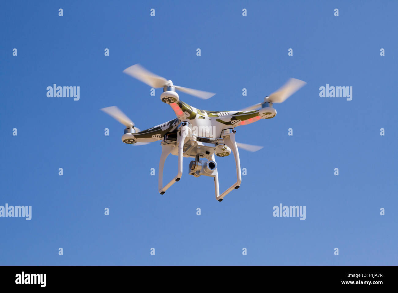 Camouflage Quadrocopter hovering with a camera against a blue sky - Stock Image