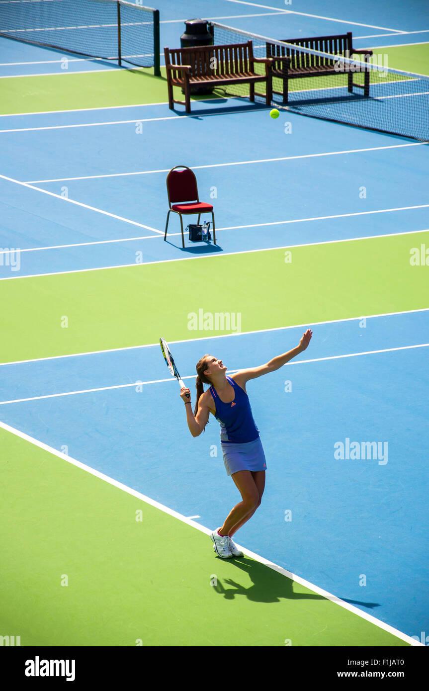 Teenage girl hitting serve on tennis court, Chiswick, London Borough of Hounslow, Greater London, England, United - Stock Image