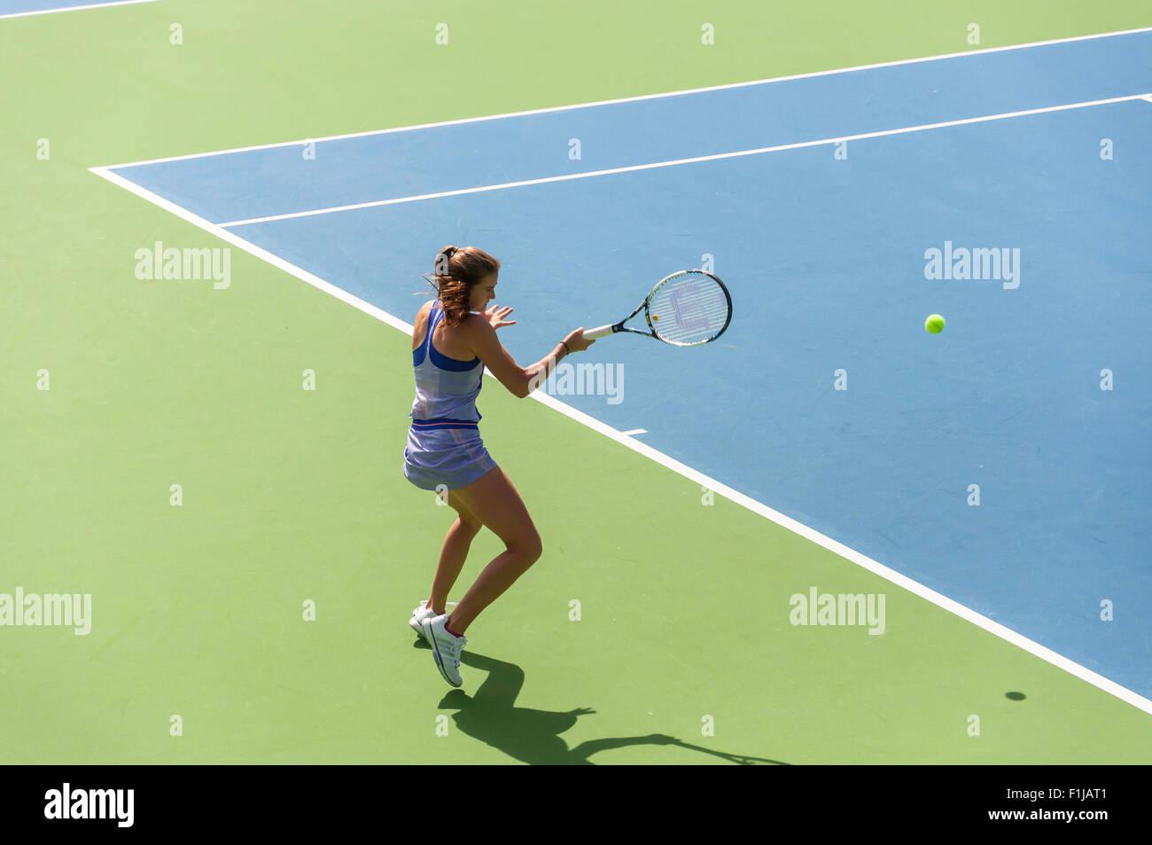 Teenage girl hitting forehand on tennis court, Chiswick, London Borough of Hounslow, Greater London, England, United - Stock Image
