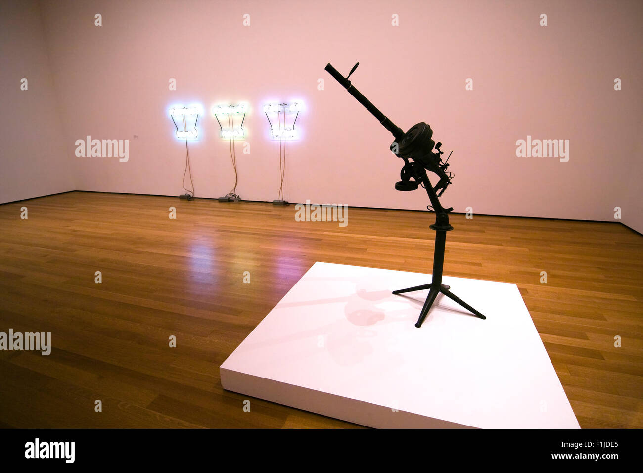 Machine Gun made out of random car parts on white pedestal in a gallery at the Museum of Modern Art in NYC Stock Photo