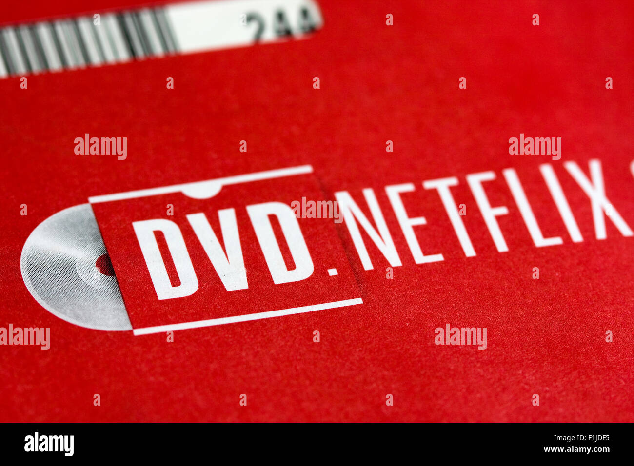 NETFLIX logo on red envelope used for returning a rented DVD by mail with sleeve barcode visible at upper left - Stock Image