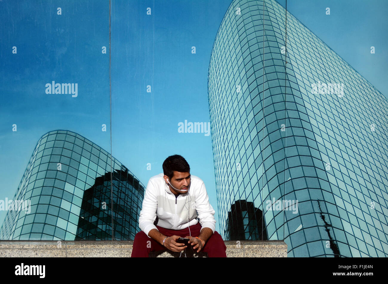 One young Indian business man talks on a smartphone outdoors  alone in city financial district street. Mobile communication - Stock Image