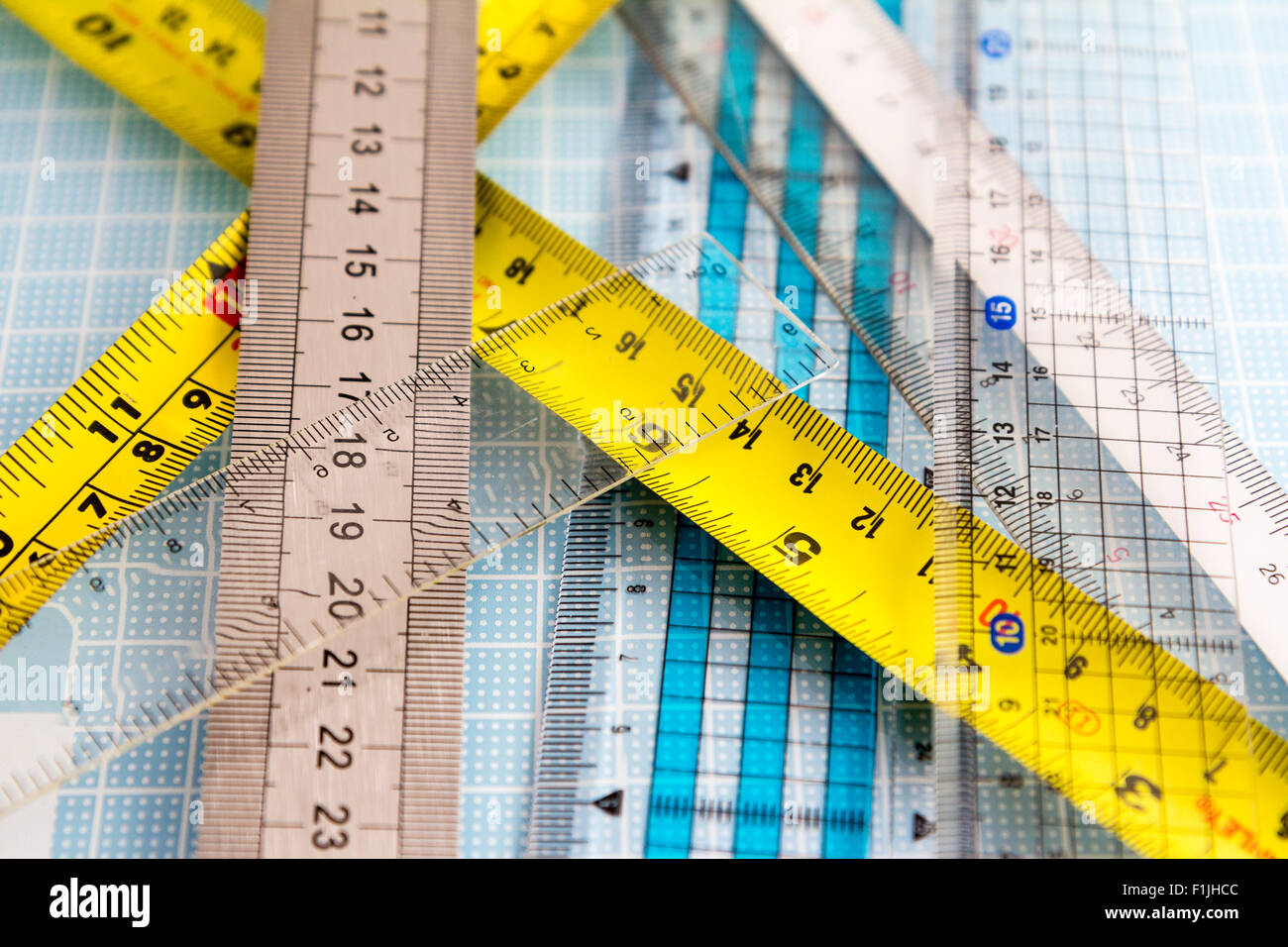 Rulers. Various types, transparetn, plastic, metal, laid out on pale blue measuring grid board - Stock Image