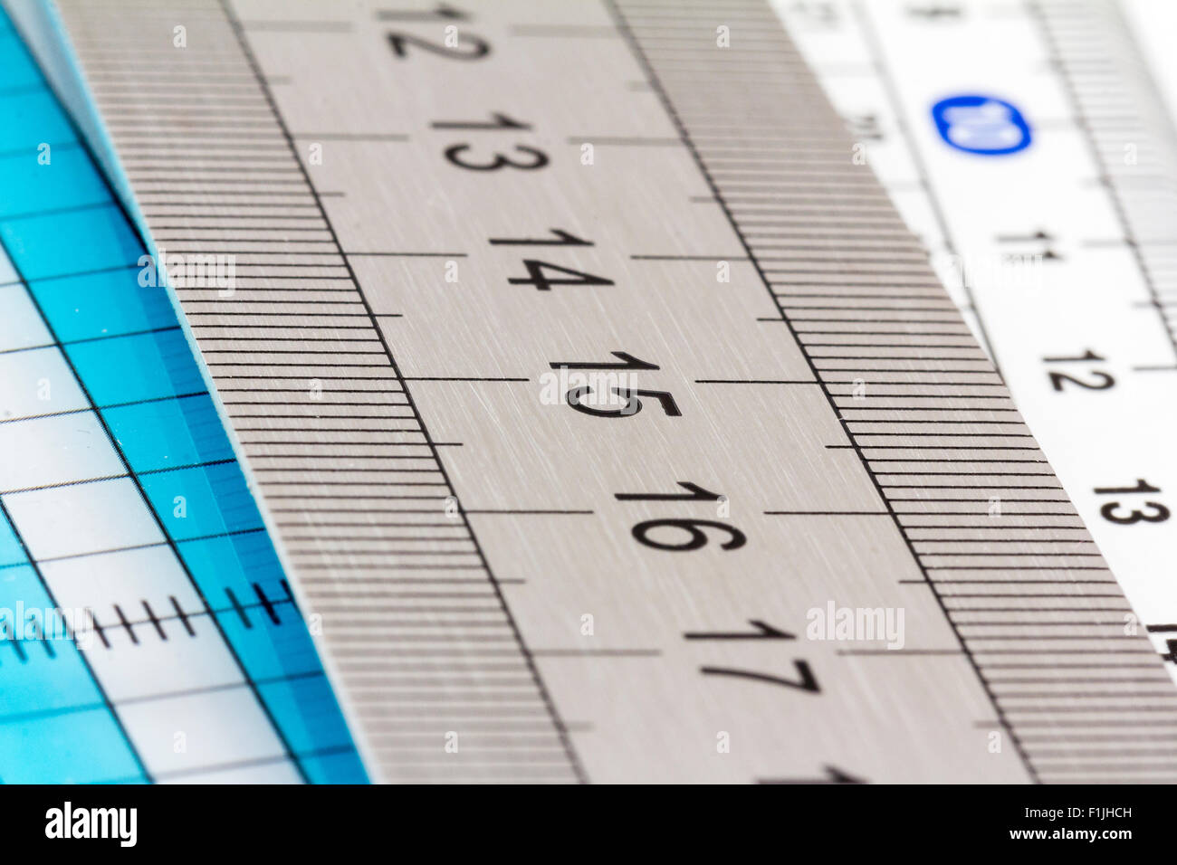 Rulers. Steel ruler, view from along, showing 13-17 cm range, resting on other plastic rulers - Stock Image