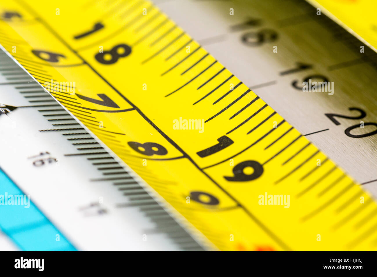 Rulers. Steel yellow roller tape ruler showing 18-19 inches on top of other rulers - Stock Image