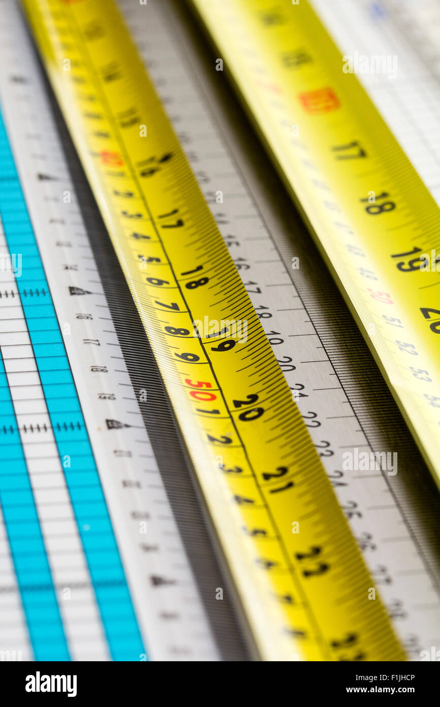 Rulers. View along various rulers and tape measures, yellow, white, blue - Stock Image