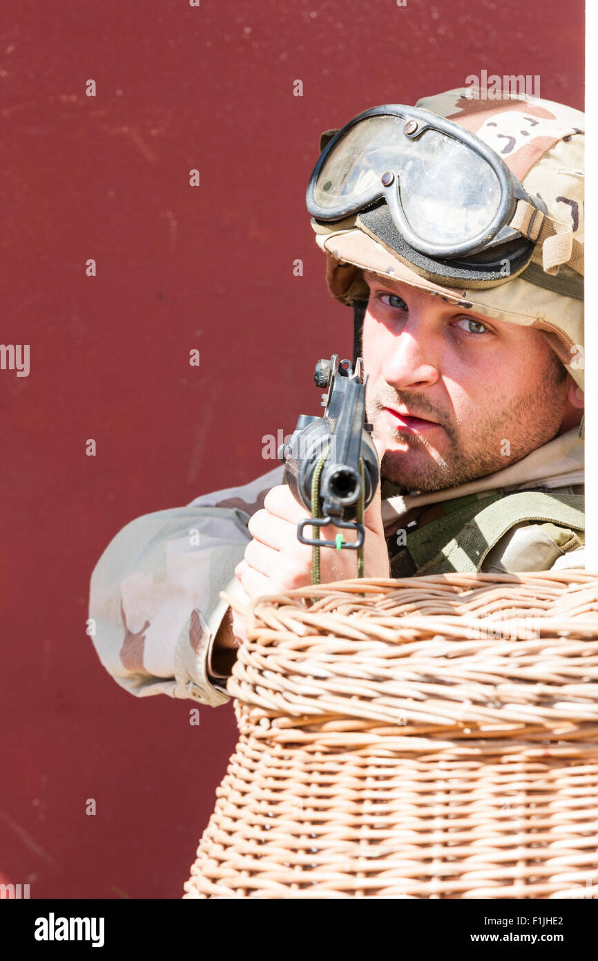 American army, black Hawk re-enactment, War and Peace show. Soldier taking aim at camera from behind basket. - Stock Image