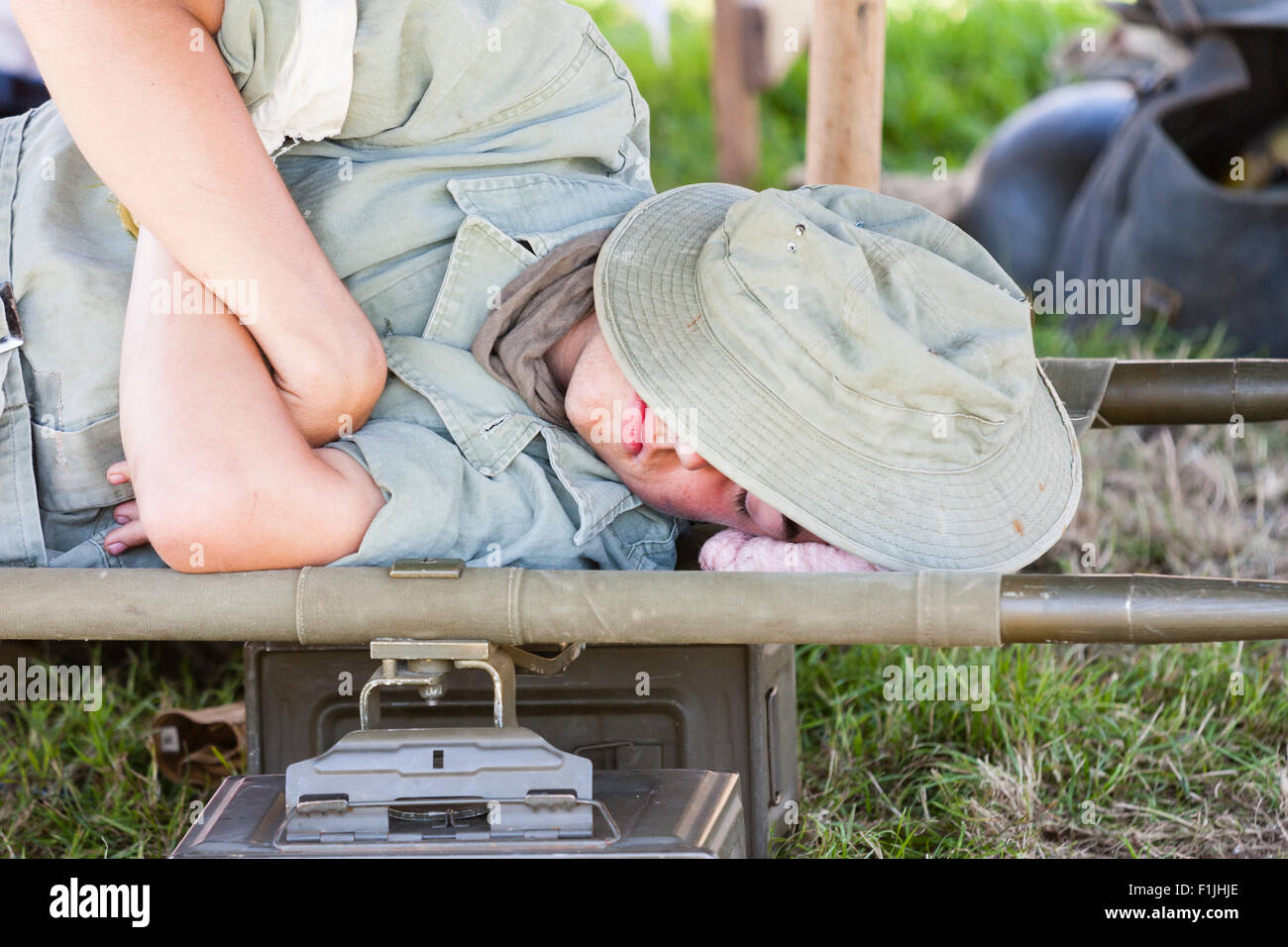 England, war and peace show. Vietnam re-enactment. Australian soldier sleeping on stretcher with hat pulled over - Stock Image