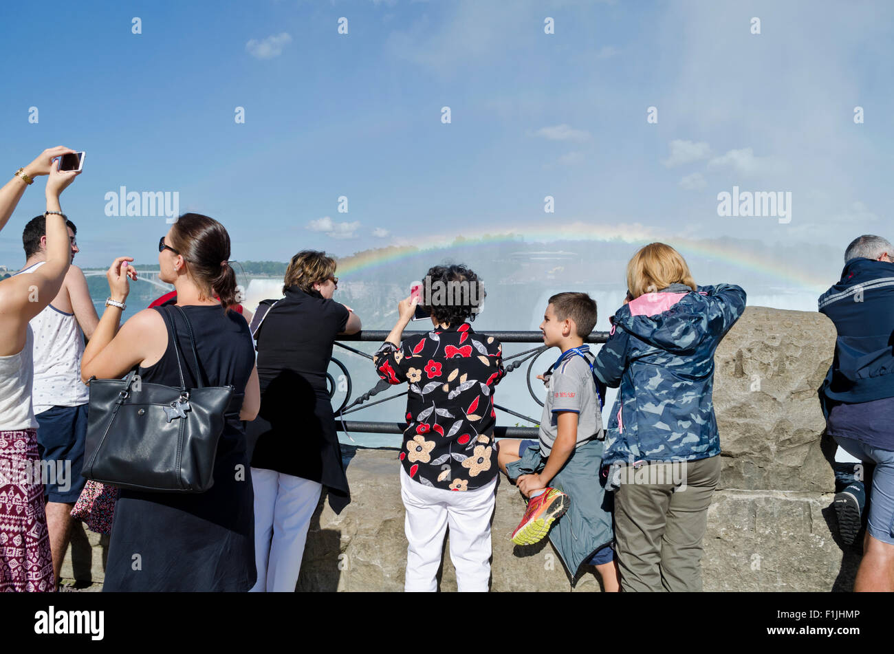 Tourists taking photos of Horseshoe Falls (Canadian) and rainbow in Niagara Falls Ontario Canada - Stock Image