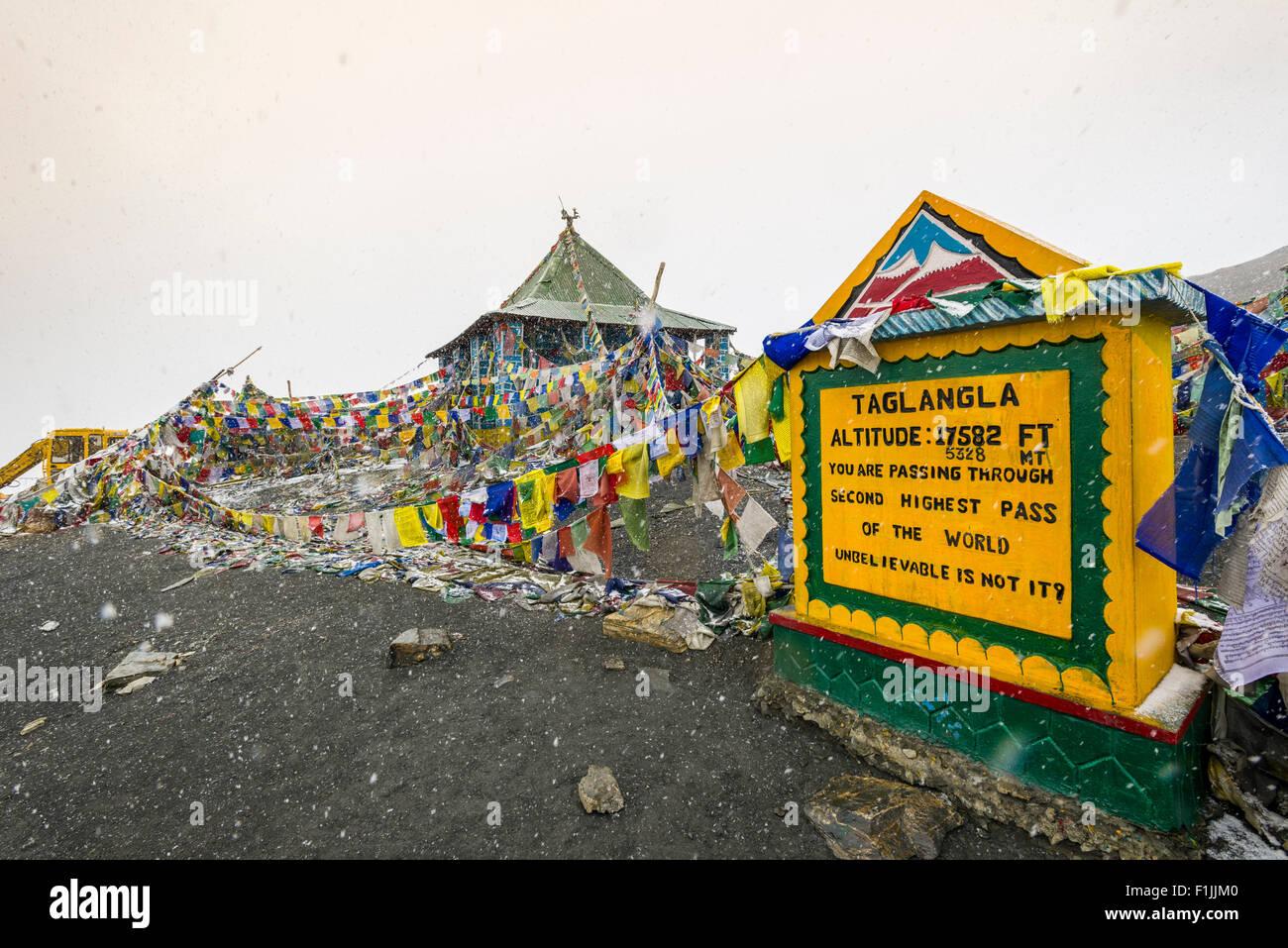 The milestone on top of Taglang La, 5,325 m, the highest pass on the Manali-Leh Highway, during snowfall, Rumtse - Stock Image