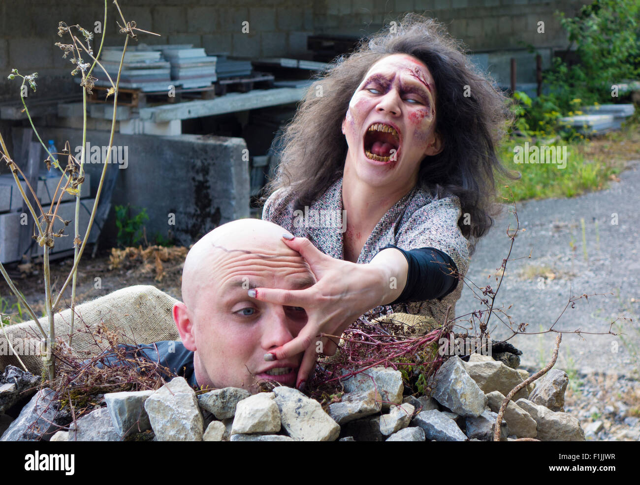 Zombie grabbing the head of a man, filming, scene from a zombie comedy, short film Brain Freeze - Stock Image