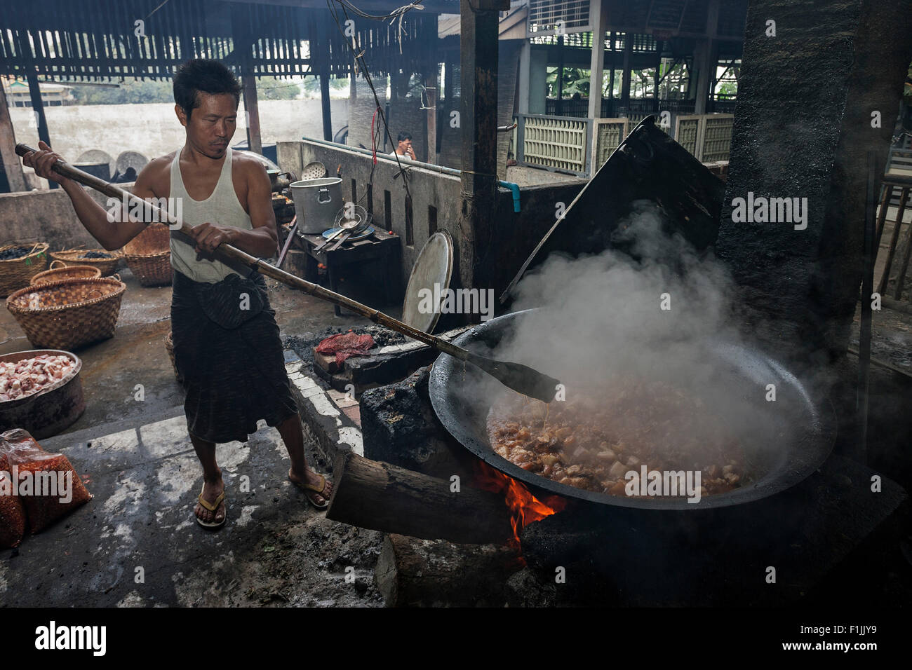 Cooking over an open fire, preparing food for the monks, catering in Mahagandayon Monastery, Amarapura, Divison - Stock Image