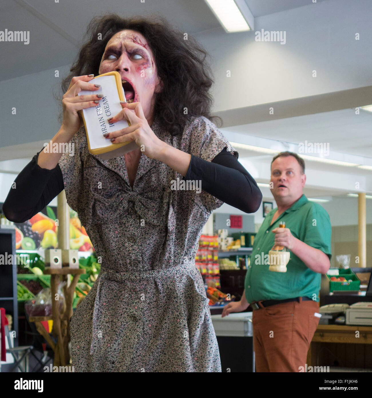 Zombie comedy, short film Brain Freeze, Zombie buying ice cream, astonished cashier behind, scene from zombie comedy - Stock Image