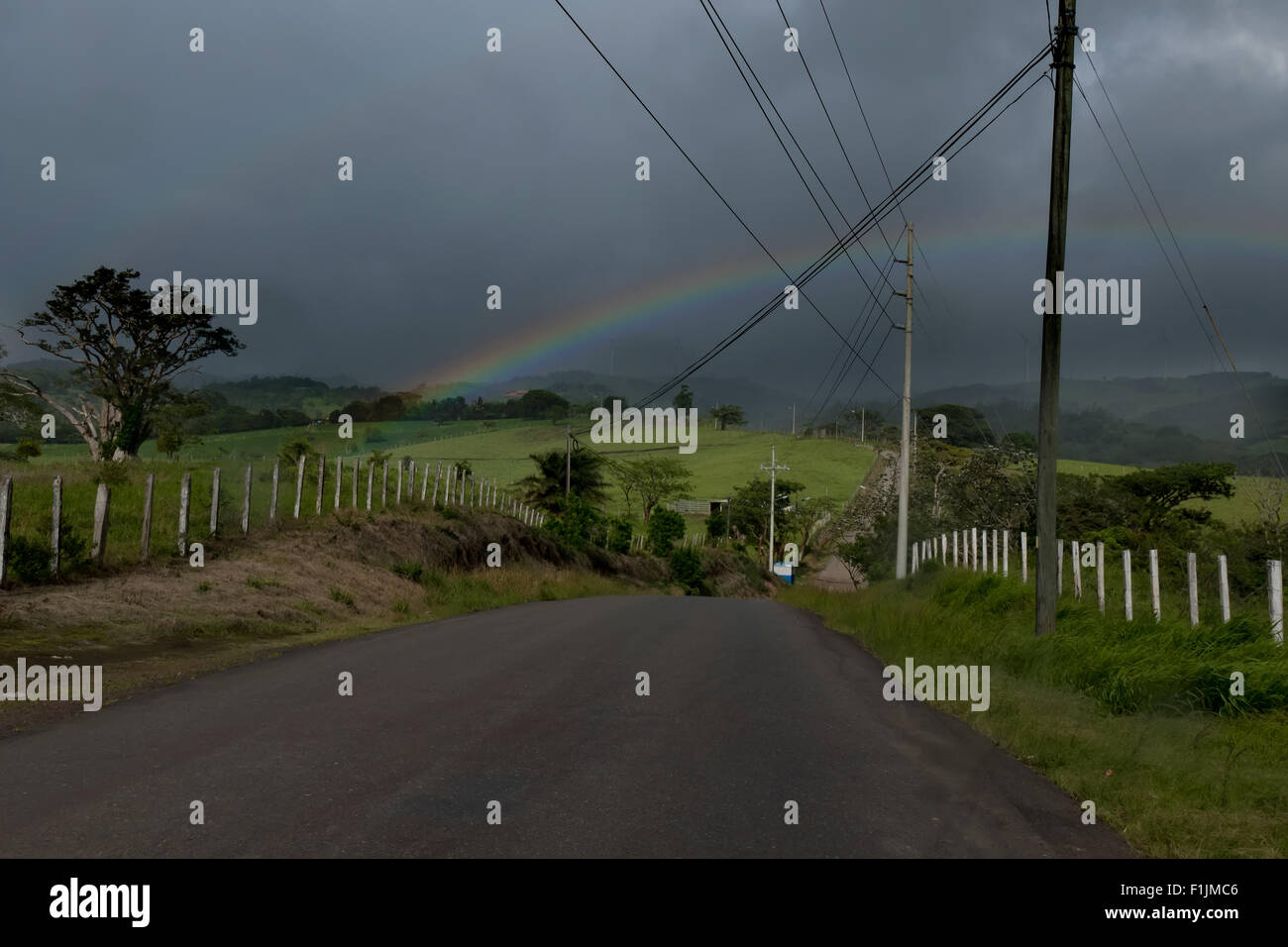 Rainbow and road, landscape after rain, rainstorm, storm in Guanacaste province, Costa Rica, Central America - Stock Image