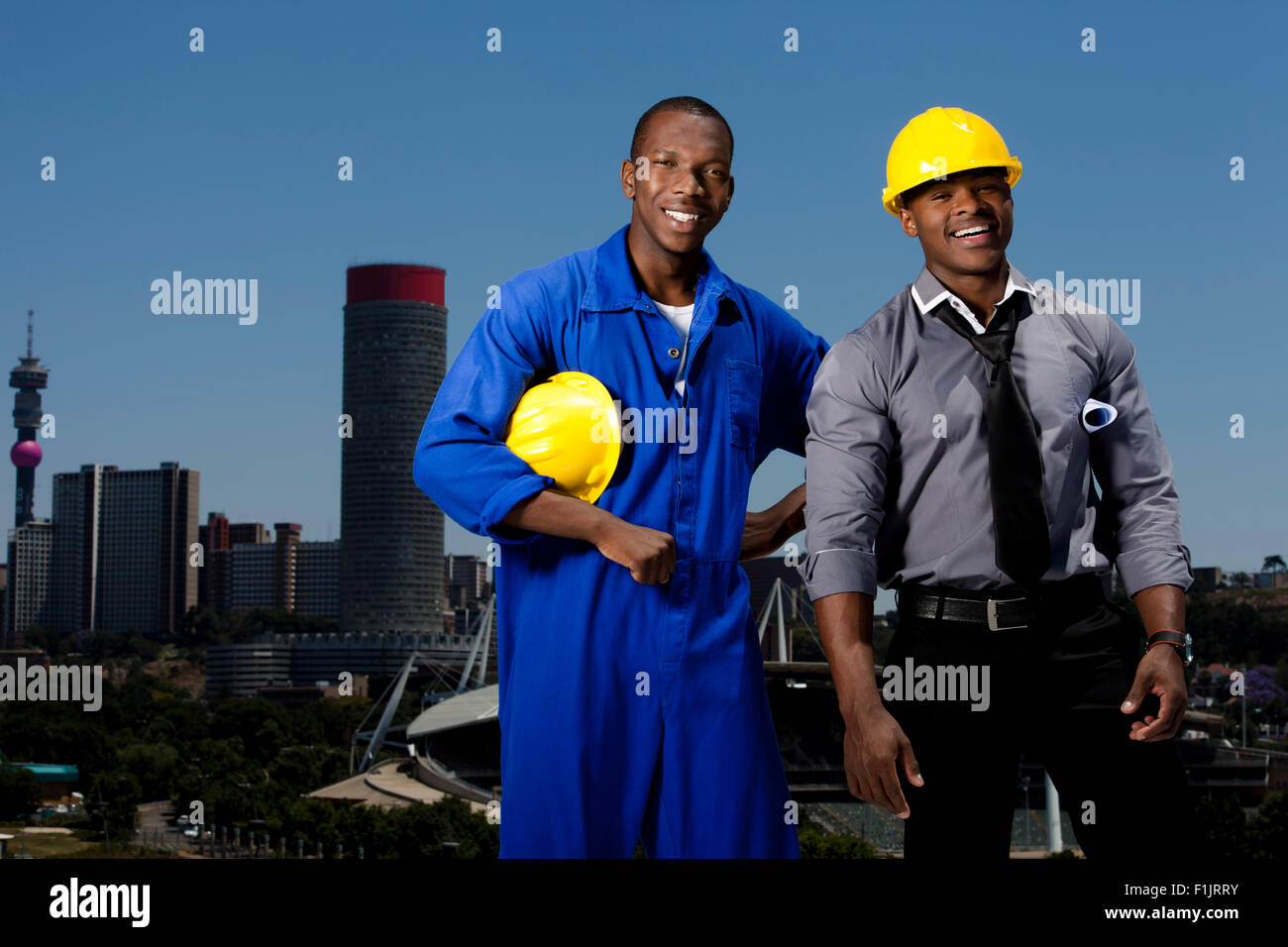 Two men with hardhats stand with cityscape in background - Stock Image