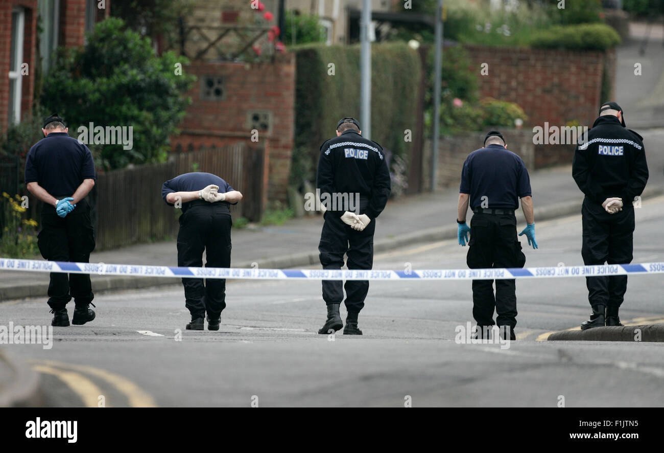 Police search for clues and gather evidence in the street after a fatal shooting. - Stock Image