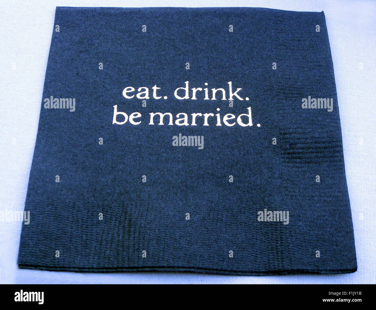 Small blue paper cocktail napkins are cleverly embossed with 'eat. drink. be married.' for a wedding reception - Stock Image