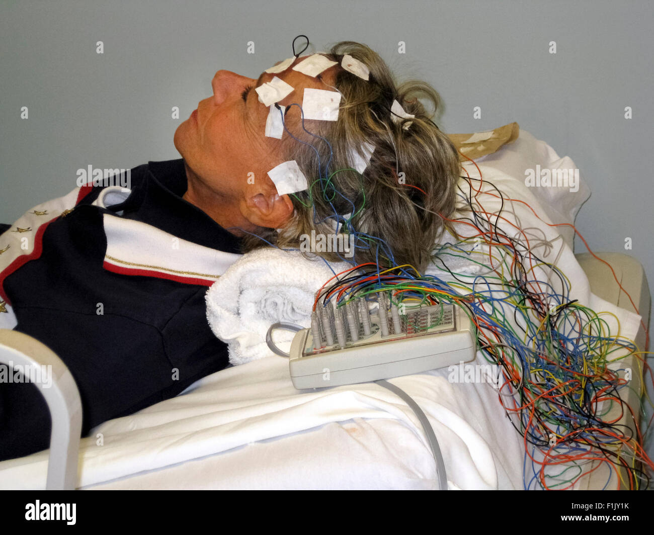 A woman in a doctor's office undergoes electroencephalogram (EEG) testing to detect abnormalities in the electrical - Stock Image