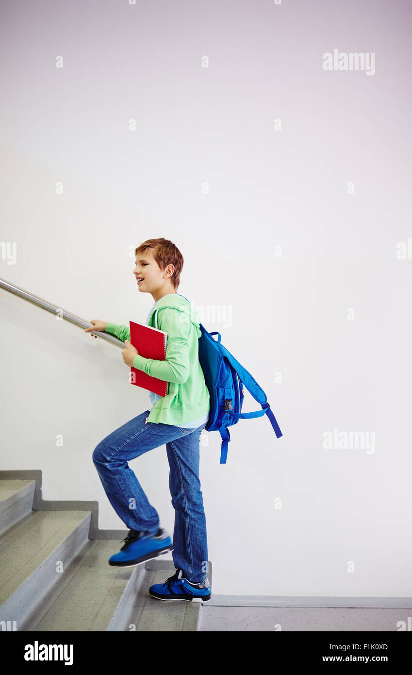 Pre-teen schoolboy with backpack going upstairs in school - Stock Image