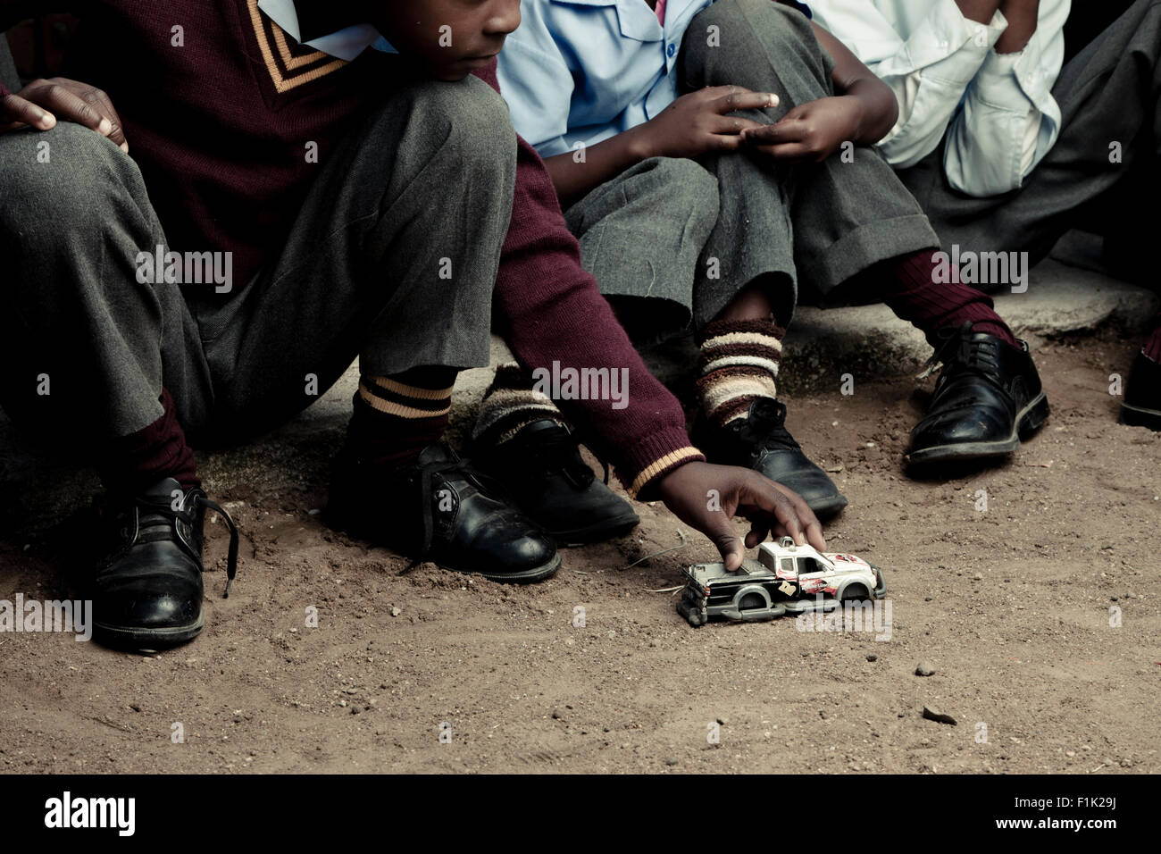 Group of African school children playing with a toy car outside - Stock Image